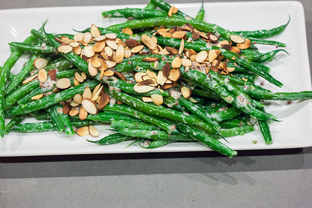 Crisp green beans are coated with a creamy, herby, whole grain mustard sauce, and topped with crunchy toasted almonds, and ready in 5 minutes! | spachethespatula.com #recipe