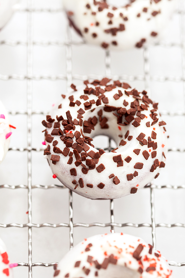 These little donuts contain extra cocoa powder for a more chocolatey red velvet. A cream cheese glaze and lots of sprinkles make them extra cute! | spachethespatula.com #recipe